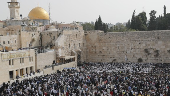 Jewish people take part in the Cohanim prayer (priest's blessing) during the Passover (Pesach) holiday at the Western Wall in the Old City of Jerusalem on April 13, 2017, with the Dome of the Rock seen in the background.