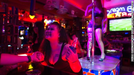 PATTAYA,THAILAND -JULY 31, 2016:  Bar girls entertain men at a bar along the Walking Street where bars and sex scenes are a commonplace July 31, 2016 in Pattaya, Thailand. Thailand's first female minister of tourism would like the sex trade that is a huge business in the country to be banned. Tourists flock to Thailand for many sights including beautiful beaches but also for sex tourism. Cities like Bangkok and Pattaya are well known as hubs of the Southeast Asian sex trade, despite the fact that prostitution has been illegal in Thailand since 1960.(Photo by Paula Bronstein/ Getty Images)