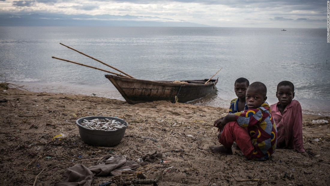 Children sit next to a bucket filled with fish on the shores of Lake Tanganyika in Uvira, Democratic Republic of Congo. One of Africa's Great Lakes, Tanganyika is the second largest in the continent, behind Lake Victoria. Bordering the DRC, Tanzania, Zambia and Burundi, the lives of millions living on its shores are under threat as the lake's ecosystem changes.