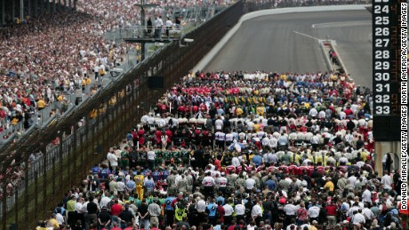 The field of drivers and their teams stand for the national anthem before the Indianapolis 500 in 2008.