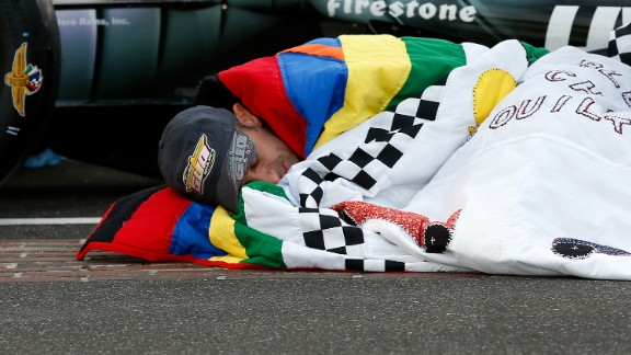"""Since 1976, Jeanetta Holder, a long-time fan of the Indy 500, has produced a custom-made quilt for the winner, earning her the title """"Quilt Lady."""" Here, 2013 champion Tony Kanaan snuggles up in his prize blanket."""