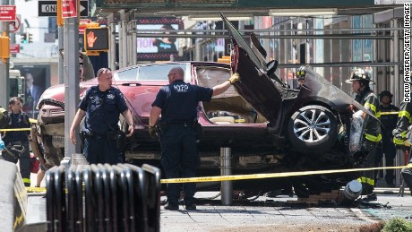 A wrecked car sits in the intersection of 45th and Broadway in Times Square.