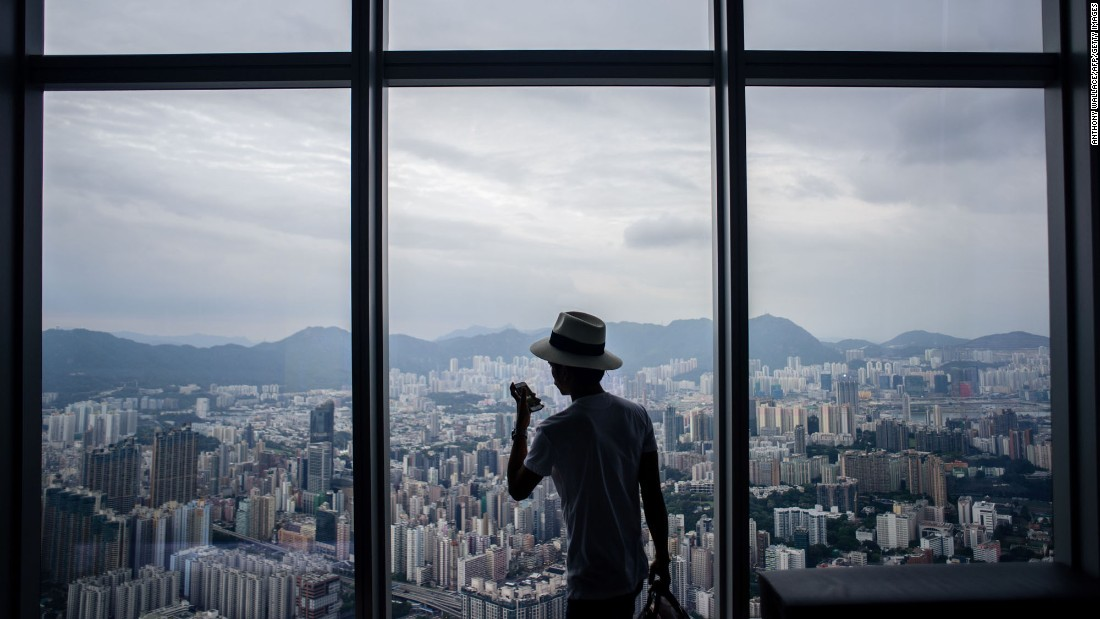 A visitor takes photos of Hong Kong's Kowloon district from the viewing deck of the International Commerce Centre on Tuesday, May 16.