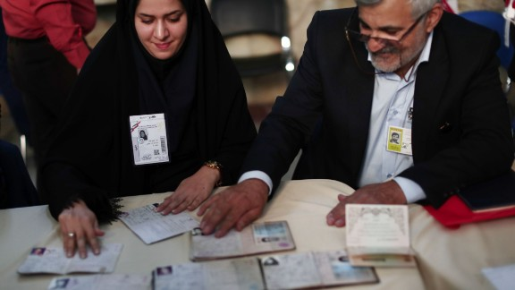 Election officials check people's ID cards at a polling station in Tehran on May 19, 2017. Iranians head to the polls for a vote that has become a referendum on President Hassan Rouhani's policy of opening up to the world and efforts to rebuild the stagnant economy. / AFP PHOTO / Behrouz MEHRI        (Photo credit should read BEHROUZ MEHRI/AFP/Getty Images)