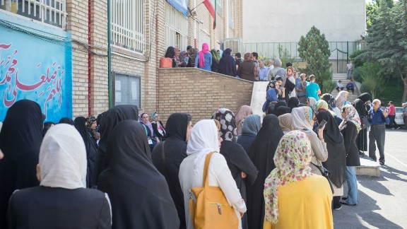 Iranians queue to cast their votes at a polling station in Tehran.