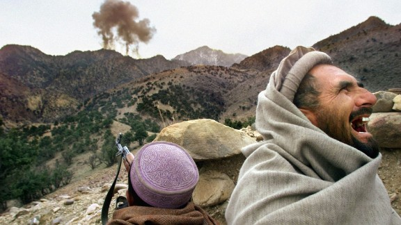 A Northern Alliance fighter bursts into laughter as US planes strike a Taliban position near Tora Bora, Afghanistan, in December 2001.