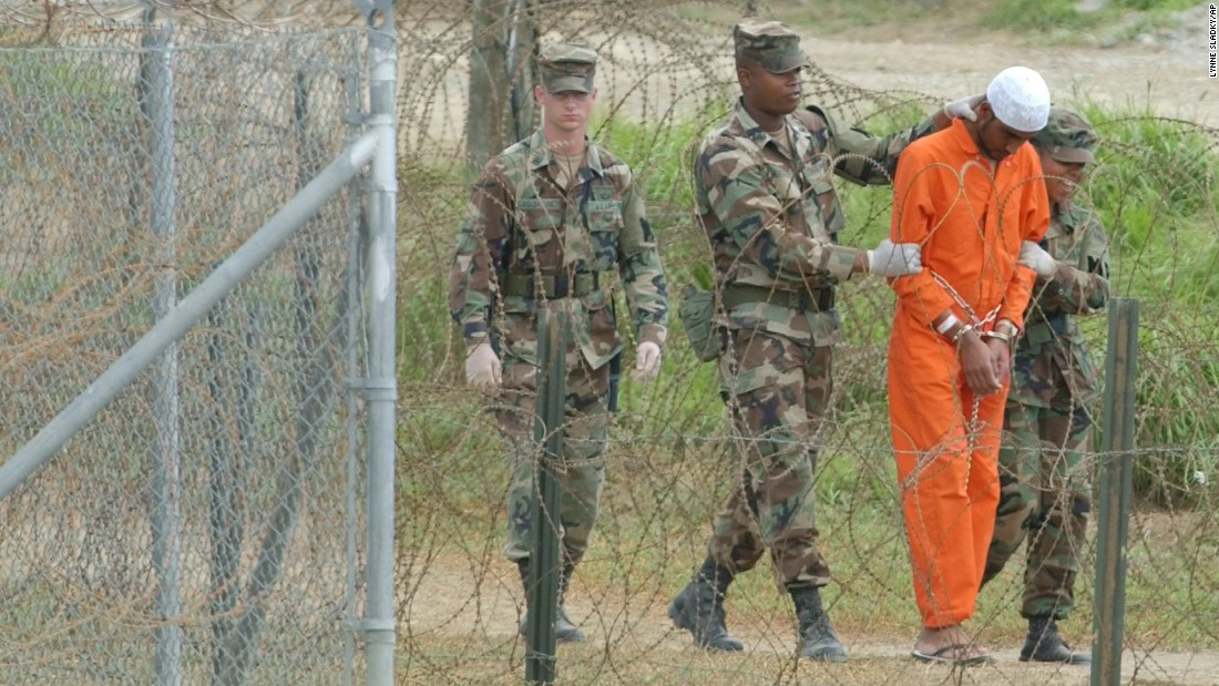 "A detainee is escorted by military police at the US naval base in Guantanamo Bay, Cuba, on February 6, 2002. The base's detention facilities had been repurposed to hold detainees from the US ""war on terror."""