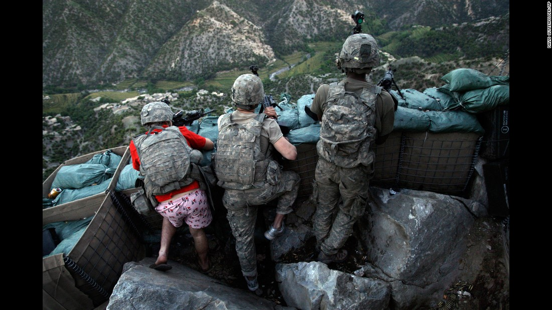 "US soldiers take defensive positions after receiving fire from Taliban positions in Afghanistan's Kunar Province on May 11, 2009. Army Spc. Zachary Boyd, left, was wearing ""I love NY"" boxer shorts after rushing from his sleeping quarters to join his fellow platoon members."