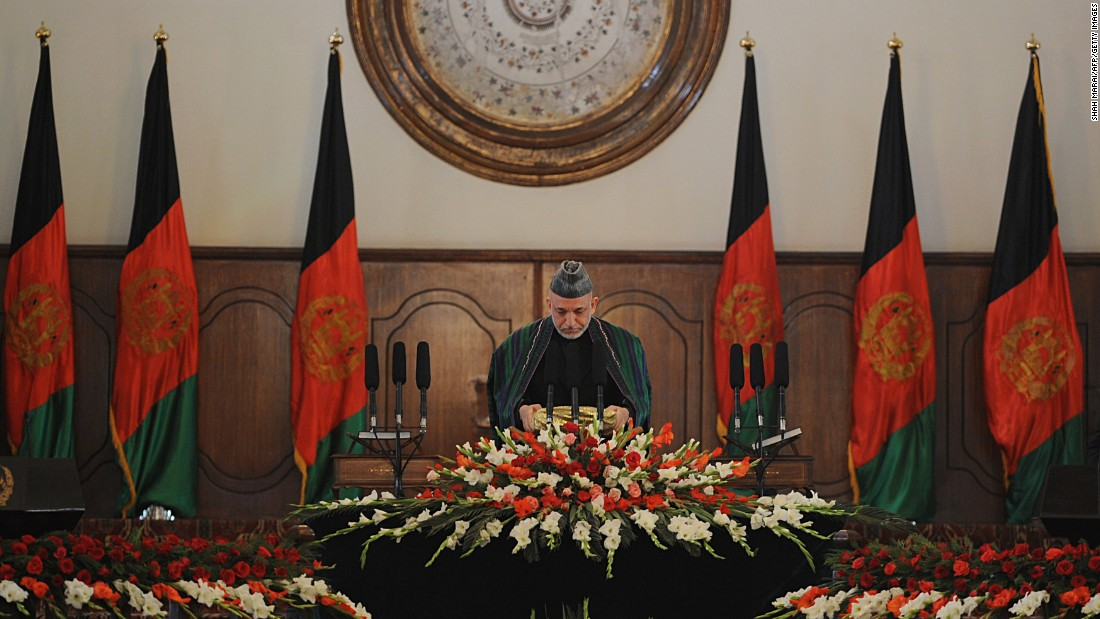Afghan President Hamid Karzai prepares to kiss a copy of the Quran during his swearing-in ceremony on November 19, 2009. He won a second term after Foreign Minister Abdullah Abdullah dropped out of a runoff.
