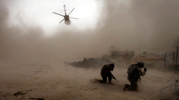 US soldiers shield themselves from dust as a helicopter takes off in Afghanistan's Arghandab Valley on July 30, 2010.
