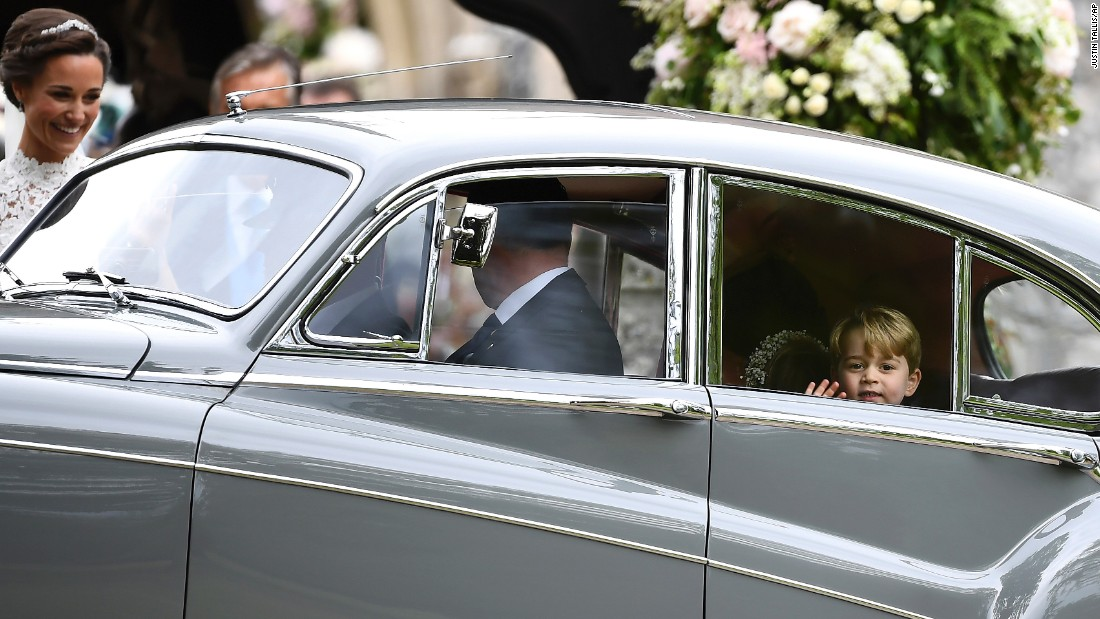 Prince George waves as he leaves in a car after attending his aunt's wedding.