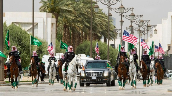 Soldiers on horseback carry the US and Saudi flags as they escort Trump to the Saudi Royal Court in Riyadh.