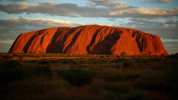 ULURU-KATA TJUTA NATIONAL PARK, AUSTRALIA - NOVEMBER 27:  (EDITORS NOTE: Exposure latitude of this image has been digitally increased.) Uluru is seen at as the sun sets on November 27, 2013 in Uluru-Kata Tjuta National Park, Australia. Uluru/ Ayers Rock is a large sandstone formation situated in central Australia approximately 335km from Alice Springs. The site and its surrounding area is scared to the Anangu people, the Indigenous people of this area and is visited by over 250,000 people each year.  (Photo by Mark Kolbe/Getty Images)