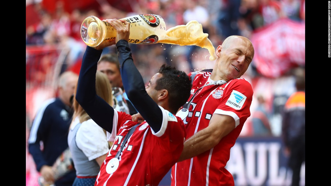 Arjen Robben is showered in beer by Bayern Munich teammate Thiago Alcantara as the German soccer club celebrated its fifth straight league title on Saturday, May 20.