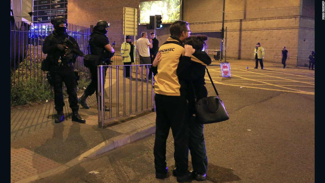 People hug near armed police who responded to the scene.