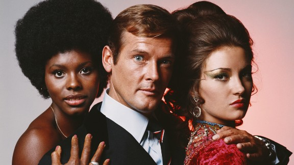 """English actor Roger Moore is flanked by Gloria Hendry, left, and Jane Seymour in this photo from the James Bond movie """"Live and Let Die"""" in 1973. Moore, who portrayed Bond in seven films, <a href=""""http://www.cnn.com/2017/05/23/entertainment/roger-moore-dies/"""" target=""""_blank"""">died Tuesday, May 23,</a> at the age of 89."""