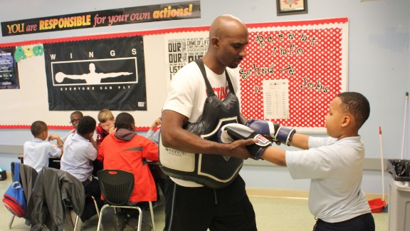 After-school instructor Clemon Clay teaches Justice Watkins boxing moves.