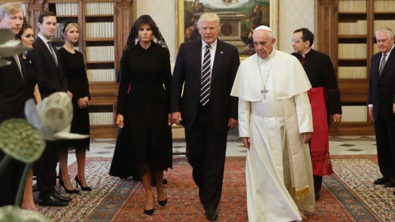Pope Francis (R) walks along with US President Donald Trump (C) and US First Lady Melania Trump during a private audience at the Vatican on May 24, 2017.