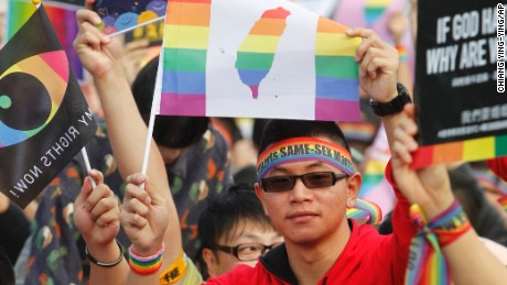 A supporter of LGBT and human rights holds a rainbow flag with Taiwan map during a rally supporting a proposal to allow same-sex marriage in Taipei, Taiwan, Saturday, Dec. 10, 2016.