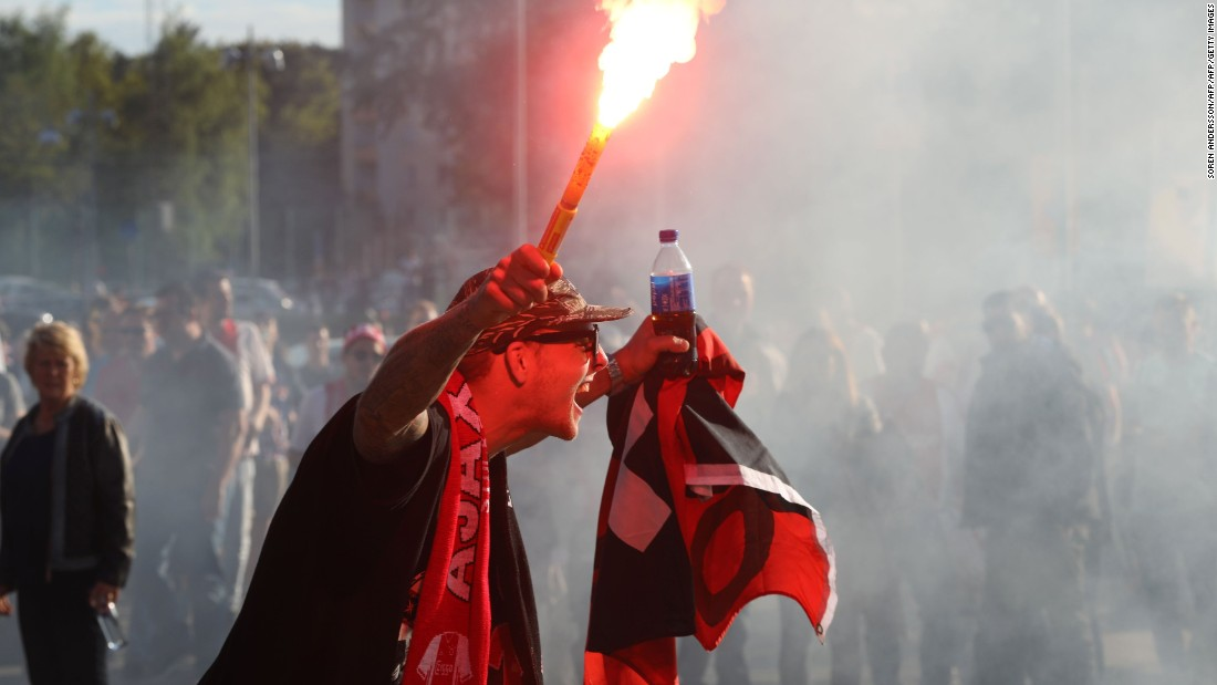 An Ajax supporter holds a lit flare prior to kick off.