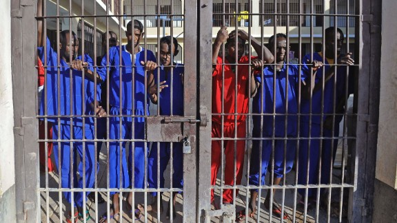 Somali prisoners convicted of piracy, stand behind a gate of the prison in Garowe, Puntland state, in northeastern Somalia, on December 14, 2016.  However, security firms complain that pirates are receiving light sentences that do not deter them from repeat offenses.