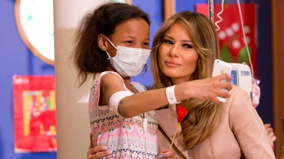 A girl takes a selfie with Melania Trump at a children