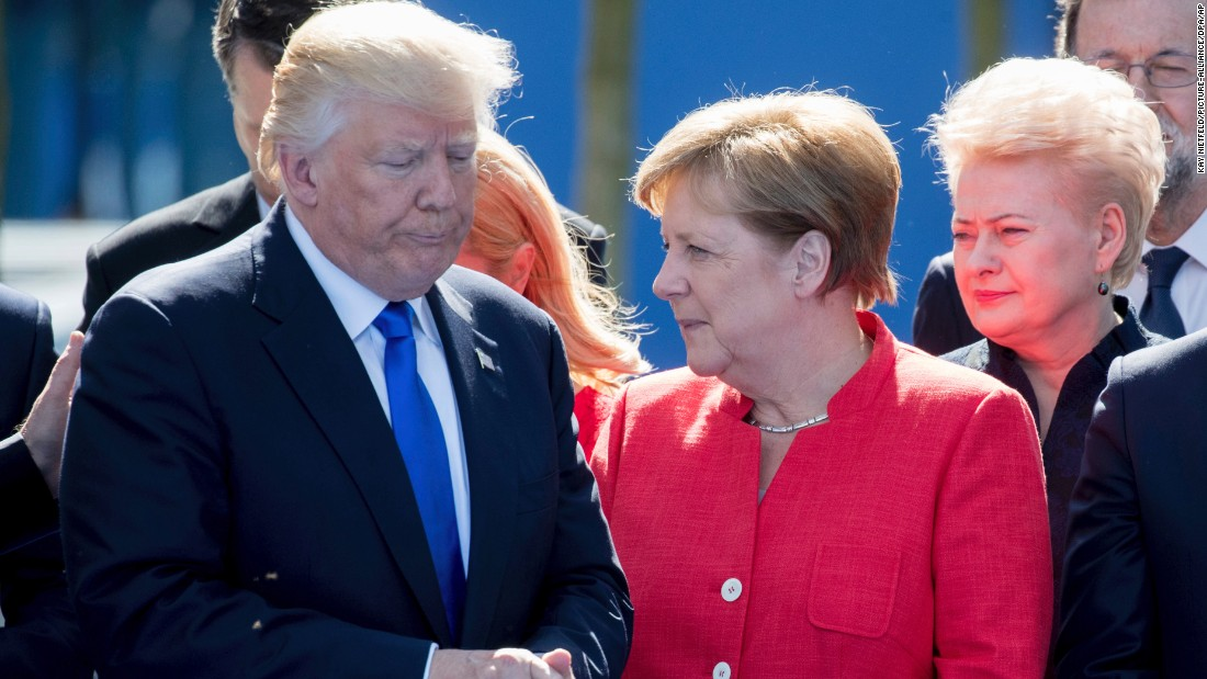 Trump stands next to German Chancellor Angela Merkel at the NATO summit.
