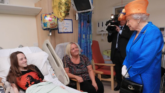 Britain's Queen Elizabeth II speaks to 15-year-old Millie Robson and her mother, Marie, during a visit to the Royal Manchester Children's Hospital on May 25. The Queen was visiting those injured in the attack.