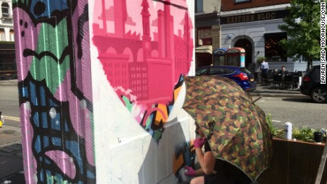 A Manchester street artist works on his tribute in the city's Northern Quarter on Thursday.
