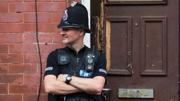 A police officer guards a house in Manchester as investigations continued on May 25. Police say a man carrying explosives acted as a lone attacker and died in the blast.