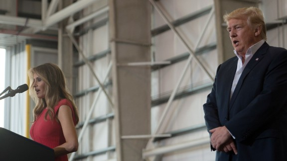 US President Donald Trump listens as his wife, First Lady Melania Trump recites the Lord's Prayer during a rally in Melbourne, Florida on February 18, 2017.