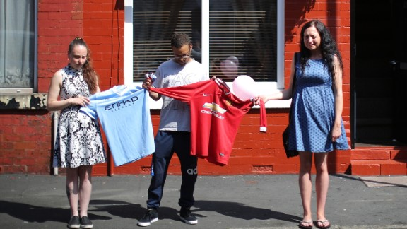 Local residents hold Manchester City and Manchester United soccer jerseys during the national minute of silence.