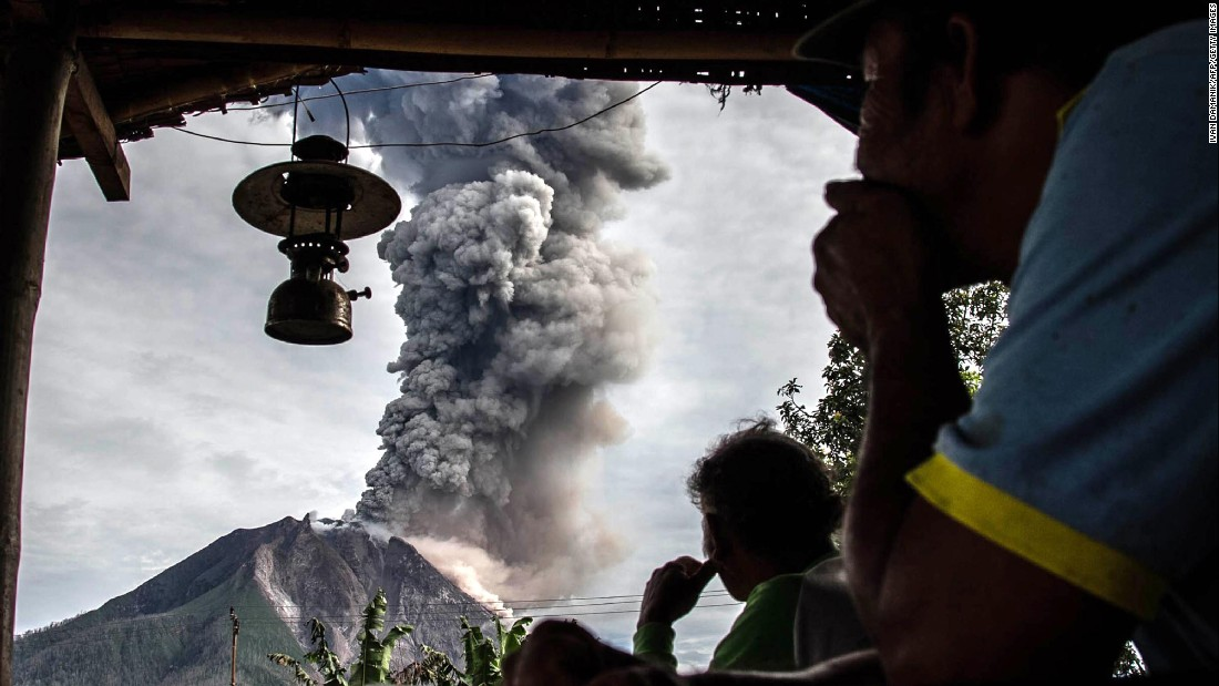 Villagers look on as Mount Sinabung volcano spews thick volcanic ash in Karo, Indonesia, on Friday, May 19.