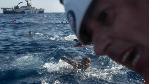 Refugees and migrants swim towards a rescue craft as a rescue crewmember from the Migrant Offshore Aid Station (MOAS) 'Phoenix' vessel pulls a man on board.