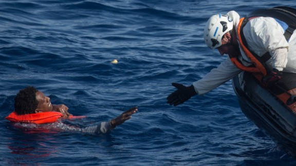 "A rescue crewmember from the Migrant Offshore Aid Station ""Phoenix"" vessel reaches out to pull a man into a rescue craft on May 24."