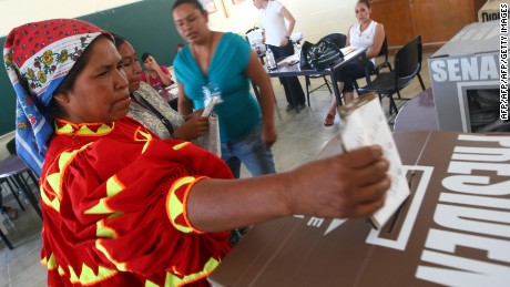 A Taraumara indigenous woman in traditional clothes casts her vote at a polling station in the northern border city of Ciudad Juarez, Mexico during elections on July 1, 2012. Voters, exhausted by violence, seem prepared to bring the Institutional Revolutionary Party (PRI), which ran the country for seven decades, back to office. Mexican presidents are elected by simple majority for six-year terms and are banned from running for reelection.  AFP PHOTO/JESUS ALCAZAR        (Photo credit should read Jesus Alcazar/AFP/GettyImages)