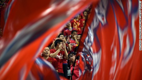 A fan (C) of China's Guangzhou Evergrande swirls a large flag during the AFC Champions League football match between China's Guangzhou Evergrande and Hong Kong's Eastern at Mongkok Stadium in Hong Kong on April 25, 2017. / AFP PHOTO / Anthony WALLACE        (Photo credit should read ANTHONY WALLACE/AFP/Getty Images)