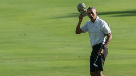 US President Barack Obama doffs his cap after putting on the 18th green at the Kapolei Golf Club in Kapolei on December 21, 2016 during his annual Christmas vacation in Hawaii. / AFP / NICHOLAS KAMM        (Photo credit should read NICHOLAS KAMM/AFP/Getty Images)