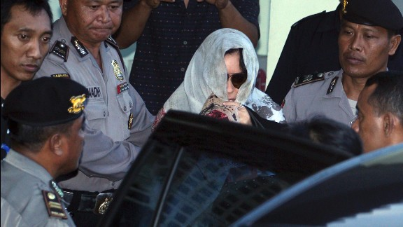 Schapelle Corby covers her head as she leaves the parole office in Bali, Indonesia, on Saturday.