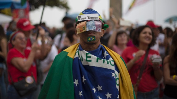 """A protester covers his face with money and a sign saying """"Temer Out."""""""