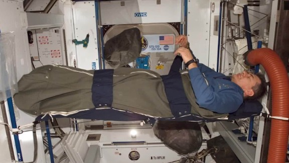 An astronaut sleeps aboard the International Space Station.