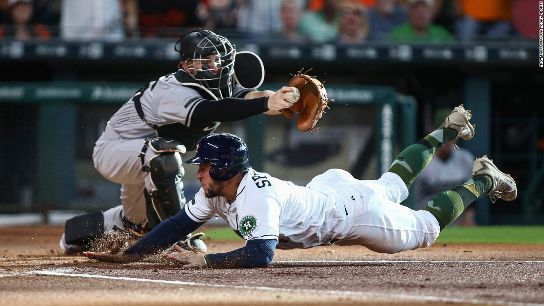 Houston's George Springer slides under Baltimore catcher Caleb Joseph during a Major League Baseball game in Houston on Saturday, May 27.