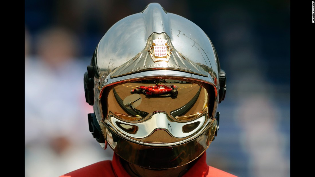 The Formula One car of Kimi Raikkonen is reflected on a firefighter's helmet during practice in Monaco on Thursday, May 25.