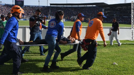 Rescue workers stretcher away a supporter injured in the stampede.