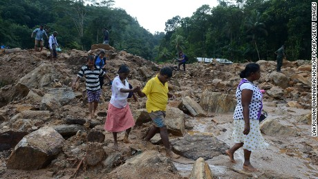 Sri Lankan villagers cross a landslide site as military rescue workers and villagers search for survivors in Athweltota village in Kalutara.