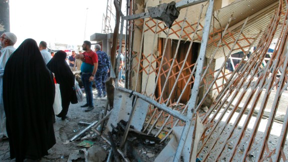 Iraqis gather at the site of a car bomb explosion near Baghdad