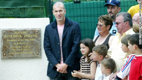 Zinedine Zidane (L) poses next to former hosts Jean-Claude (R, second row) and Nicole Elineau (Second from right, second row) during a naming ceremony of a square in Pegomas, France, in May, 2007. The couple hosted Zidane while he was a youth player with AS Cannes in 1987.