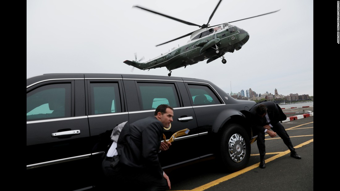 Secret Service agents use a presidential limousine to take cover from spraying water as Marine One lands in New York on Thursday, May 4.