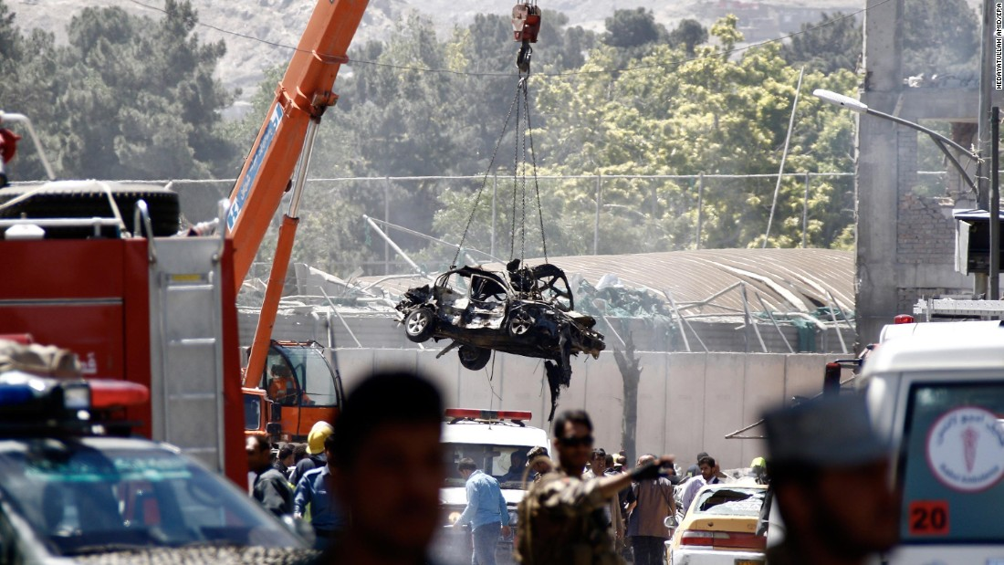 A mangled vehicle is lifted out of the wreckage after  the explosion.