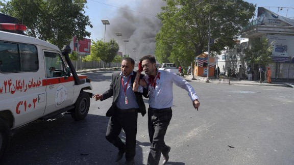 A wounded man is helped away from the scene of the attack, which struck in the midst of Kabul's morning rush hour.